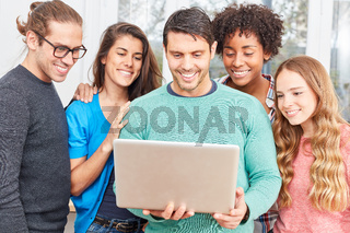 Studenten mit Laptop freuen sich über Innovation