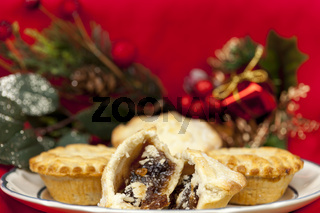 Broken mince pie on a plate with some christmas decorations