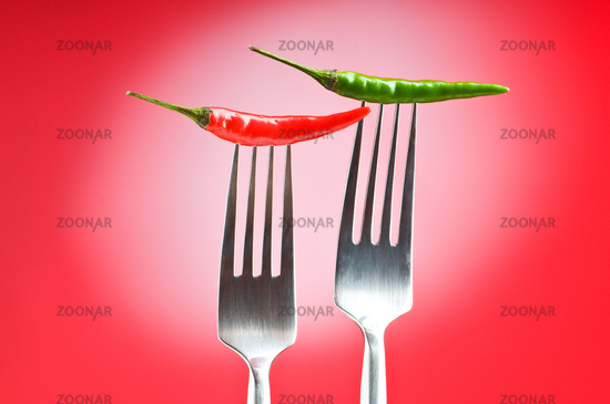 Hot pepper on the fork against colour background