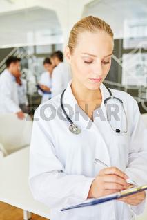 Ärztin schreibt in eine Patientenakte