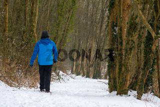 A lone man in warm winter clothes walks along a winding snow covered forest path.