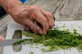 Schnittlauch am Teller mit einem Messer händisch schneiden