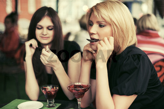 Two young women eating dessert at sidewalk cafe
