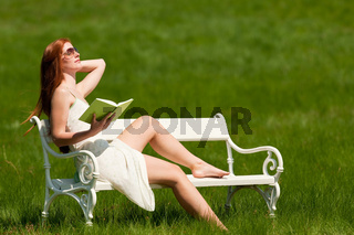 Red hair woman reading book on white bench in spring