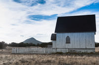 Old Fashioned white wooden church with white fence in rural setting at sunset.