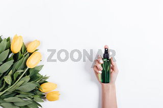 Female hand with manicure holds a green plastic bottle of water near yellow tulips, view from top