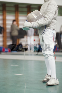 Participant of the fencing tournament with rapier and protective mask in hands