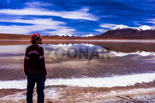 Young traveler mesmerized by Amazing colorful landscape of mirror lagoon in desert nearby Uyuni