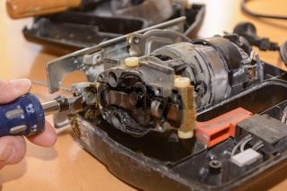 Heimwerker repariert kaputte Stichsäge mit Schraubenzieher  - Detailaufnahme