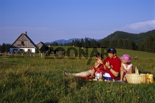 Vater macht mit seinen Töchtern ein Picknik auf der Almwiese am Ebenforst im Nationalpark Kalkalpen