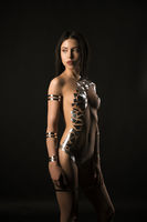 Nude brunette her body covered with gold tape