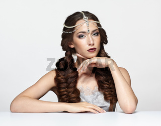 Beauty portrait of young woman in pearl diadem. Brunette girl with braids hairdo and day female makeup sit at white table