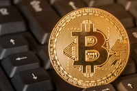 BTC coin on computer keyboard