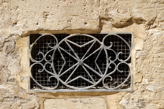 The decorative  metal ventilation grill in form of Maltese cross. Rabat. Malta