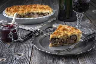 Rustic Venison Pie with cranberry relish as close-up on a plate