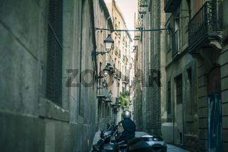 Ein Motorradfahrer in einer engen Gasse in Barcelona.