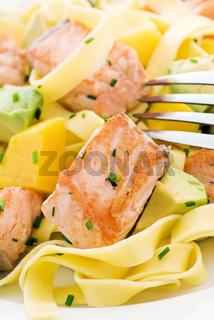 Wild salmon pieces with tagliatelle, mango and avocado as closeup on a white plate