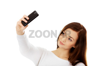 Happy young woman makes selfies with smart phone