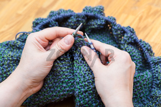 above view of female hands knit pullover from wool