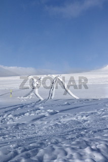 Off-piste ski slope with new-fallen snow and traces from skis, snowboards after snowfall