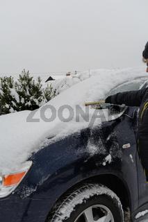 Autofahrerin kehrt mit Schneebesen Auto von Schnee ab