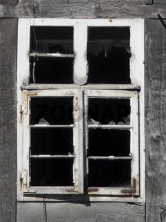Altes defektes Flügelfenster in Fachwerkfassade