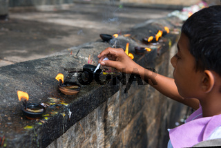 Boy prepares oil lamp to set fire it in an offerings place of the Golden cave temple