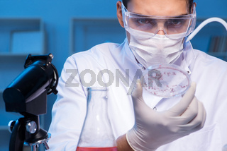 Doctor researching new virus in lab at night