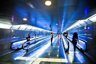 View to blue corridor with escalators and people going on it