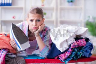 Sad woman ironing clothing at home