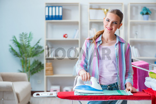 Happy housewife doing ironing at home