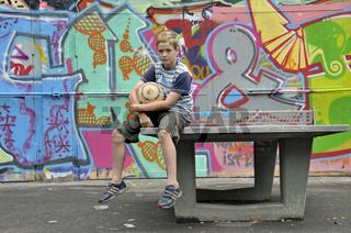 ein neunjähriger Junge sitzt mit seinem Fußball auf einer Tischtennisplatte