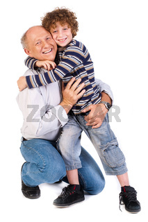 Grandson hugging his grandpa, indoors