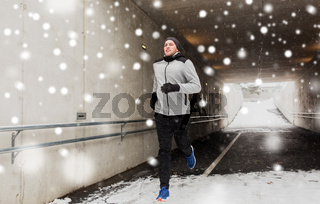 happy man running along subway tunnel in winter