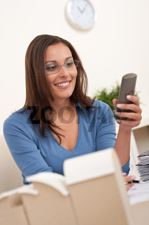 Young female architect working at office holding phone