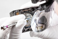 watchmaker in head magnifier repairs wristwatch