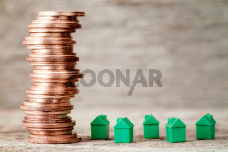Miniature houses and copper coins stack