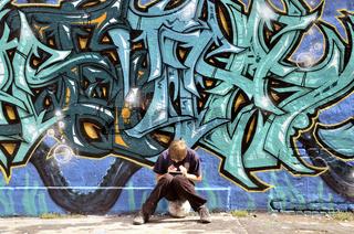 Zehnjähriger Junge spielt mit seinem Nintendo vor einer Graffitiwand, Bolzplatz, Deutschland, Europa