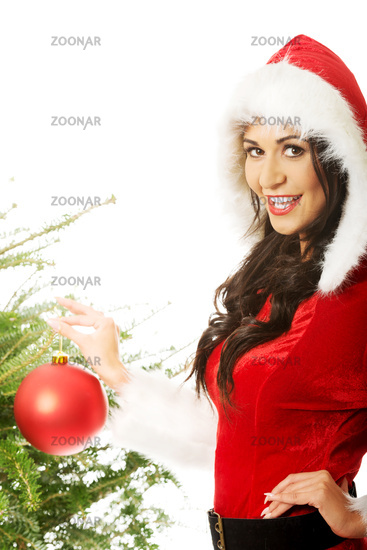Smiling woman wearing santa claus decorating christmas tree
