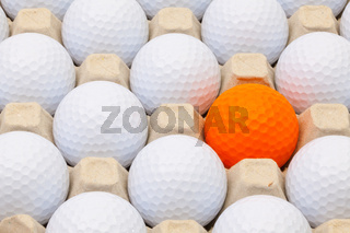 White and orange golf balls in the box eggs