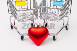 Two shopping trolley and red heard on the white desk