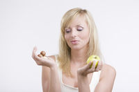 Young woman choosing between an apple and chocolat