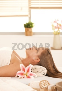 Attractive woman lying on massage bed in spa.