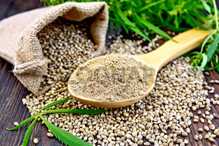Flour hemp in spoon with bag and leaf on board