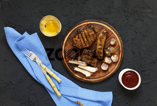 Juicy barbecue steak with ketchup and white wine on a wooden plateau. Stone black background