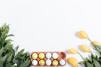 Tray with Easter eggs and yellow tulips on a white background, space for text
