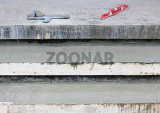 Tools: Two trowel, level on the steps and wooden formwork filled with concrete mix.