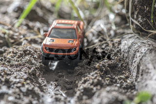 Small red off road car toy in the nature.