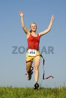 Frau läuft durch das Ziel