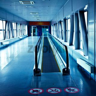 Empty blue escalator view in corridor in modern office centre
